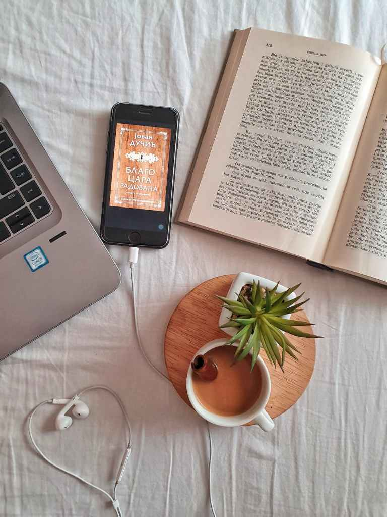 computer, iPhone connected to earphones, book and coffee mug on a tablecloth