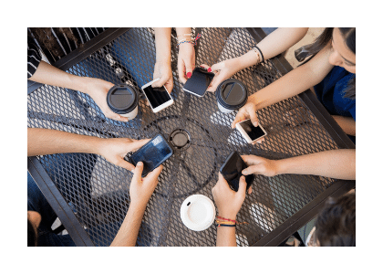 multiple hands outstretched on table holding phones/ coffee mugs in a circle