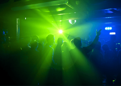 people dancing in a club with blue-green lighting