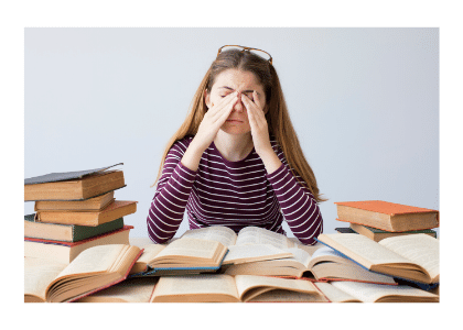 Woman studying at a desk rubbing her eyes from fatigue