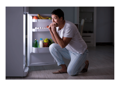 Man snacking out of the fridge late at night