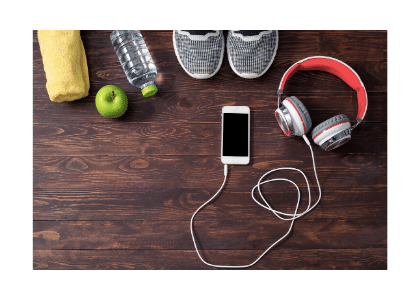 Towel, apple, water bottle, running shoes, headphones and smartphone on the floor neatly displayed
