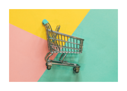 Miniature shopping trolley on a colorful background