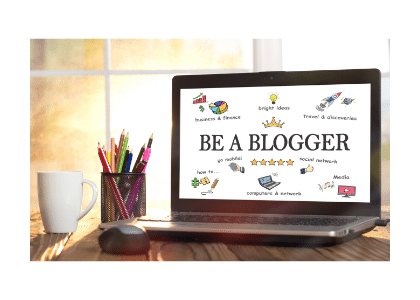 laptop on a desk with 'be a blogger' typed on the screen of the computer