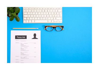 resume on blue desk with glasses keyboard and pencil