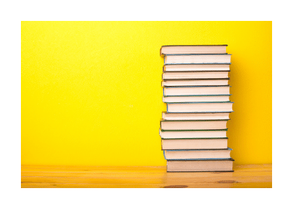 stack of books against a strong yellow background