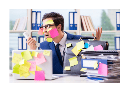 man sitting at a desk with sticky notes placed all over his desk and face