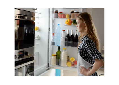 woman staring at her open fridge
